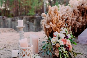 Original wedding floral decoration in the form of mini- bouquets of flowers and candles for ceremony