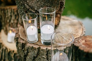 Candles in decorated goblets. Wedding decorations in rustic style. Outing ceremony. Wedding in nature.