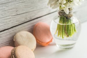 Colorful macaroons with flowers on a beautiful wooden background