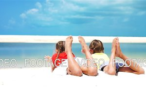 Little girls having fun at tropical beach lying together on the seashore. SLOW MOTION