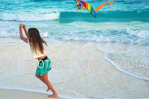 Little girl with flying kite on tropical beach. Kid play on ocean shore. Child with beach toys. SLOW MOTION