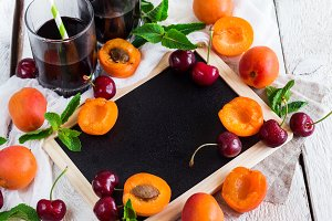 Black board with organic ripe apricots and cherries