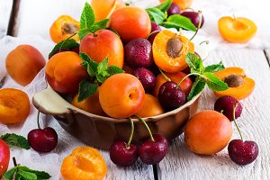 Ceramic bowl with organic ripe apricots and cherry
