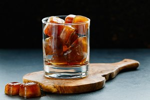 Coffee ice cubes in a glass on a wooden board on a black table.