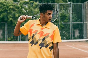 Young black man is holding a tennis racket on his shoulder