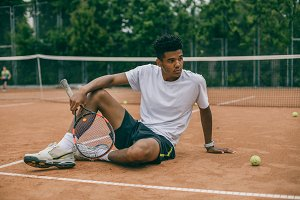 Exhausted male tennis player sitting on ground after tennis game