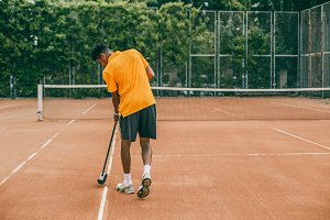 young man in a sports uniform is cleaning a tennis court