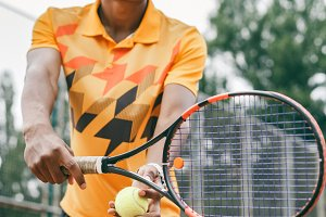 Low angle view of determined young black man playing tennis