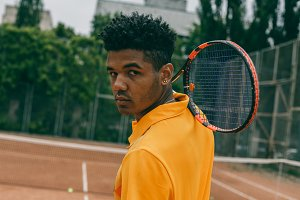 Young african man holds a tennis racket on his shoulder