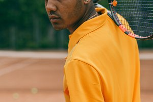 Portrait of serious african man holds a tennis racket on his shoulder