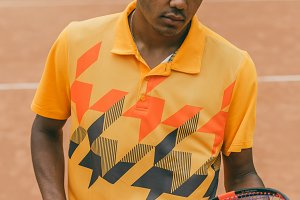 Cheerful young man in orange polo shirt holding tennis racket