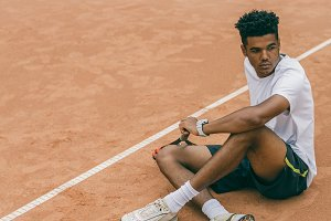Young man in sports uniform sits on the ground of a tennis court