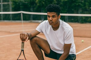 Young man hanging out in the tennis courts sitting on ground.