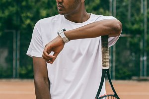 Concentrated young man holds his hand on a tennis racket.