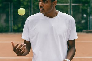 Handsome black guy in polo throws up a tennis ball on the court.