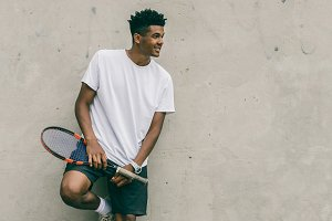 Happy young man in polo shirt holding tennis racket
