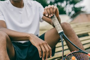 Close-up of a tennis player holding a racket sitting on a bench