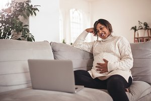 Happy pregnant woman on sofa