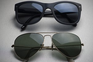 Close-up of two different types of sunglasses on gray background.