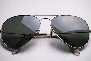Close-up of dark sunglasses with metal frame on gray background. Horizontal studio shot.
