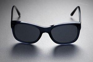 Close-up of dark sunglasses on gray background. Horizontal studio shot.