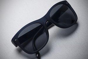 Dark sunglasses on gray background. Horizontal studio shot.