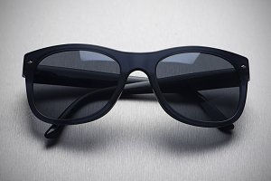 Dark sunglasses on gray background.