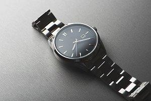Metallic wristwatch on gray background.