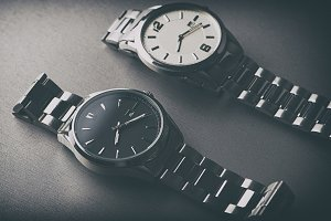 Two metallic wristwatches on gray background.