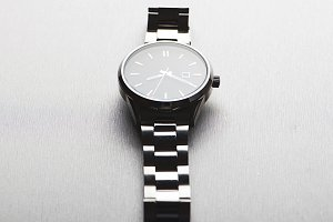 Metallic wristwatch on gray background.