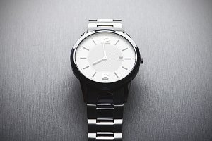 Metallic wristwatch on gray background. Horizontal studio shot.