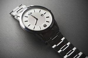 Metallic wristwatch on gray background. Horizontal studio shot.