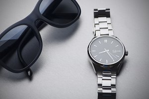 Dark sunglasses next to metallic clock on gray background. Horizontal studio shot.