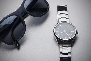 Dark sunglasses next to metallic clock on gray background. Horizontal studio shot.