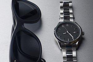 Dark sunglasses next to metallic clock on gray background. Vertical studio shot.
