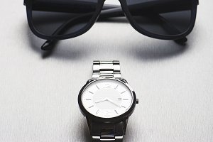 Metallic wristwatch next to sunglasses on gray background. Vertical studio shot.