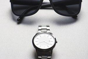 Metallic wristwatch next to sunglasses on gray background. Vertical studio shot.