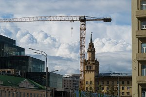 Tower crane against the blue sky and home repair