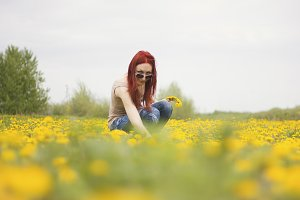 Red-haired girl in the field of dandelions
