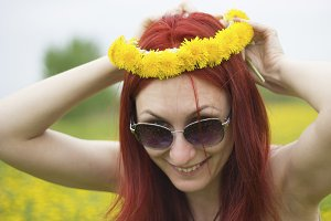 Red-haired girl with a wreath of dandelions on her head