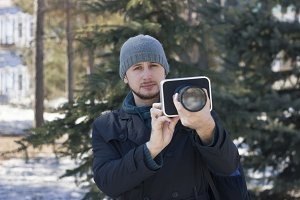 The guy with the camera in the winter forest