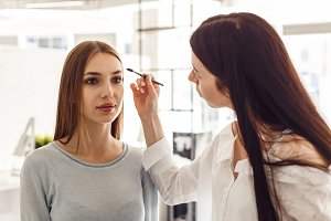 Master makeup corrects, and gives shape for eyebrows in a beauty salon.
