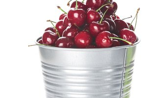 Bucket with cherries isolated on white background