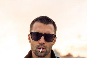 Handsome man smoke on the street.