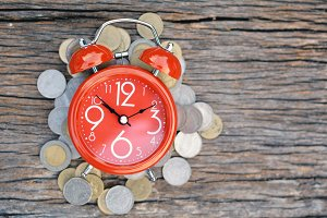 Red alarm clock and coins