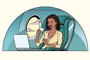 African Businesswoman in business class of the aircraft works at