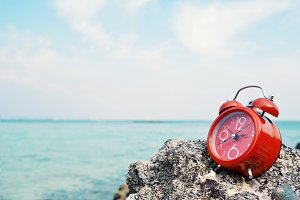 Red alarm clock on rock and sea