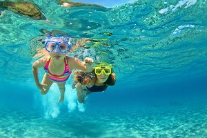 Mother with child snorkelling in sea