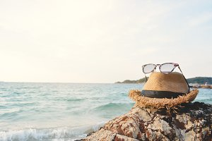 Hat and sunglasses on rock and sea