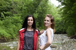 Girls blonde and brunette against the background of a mountain river and forest. Posing against the backdrop of the mountainous terrain